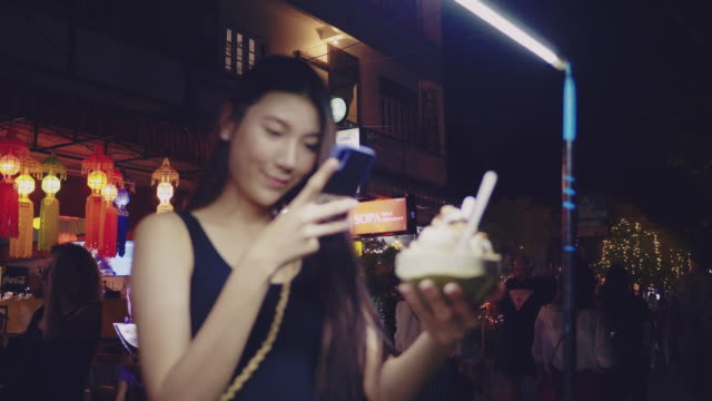 POV : Young woman taking selfie with coconut ice cream in Khao San Road.
