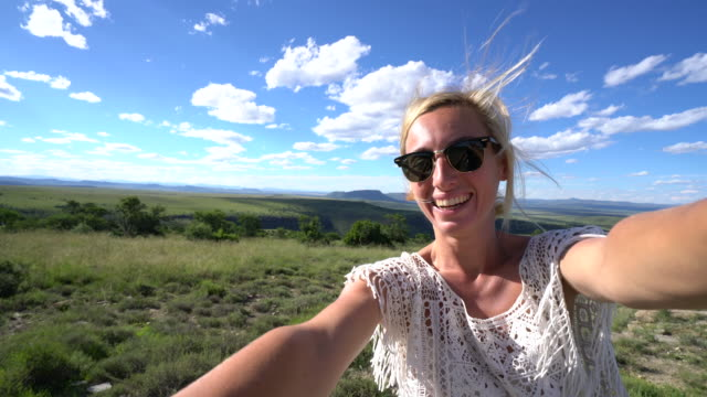 Young woman taking selfie with mountain landscape video