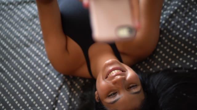 自宅でスマートフォンで selfie を取る若い女性 - スマホ ベッド点の映像素材/bロール
