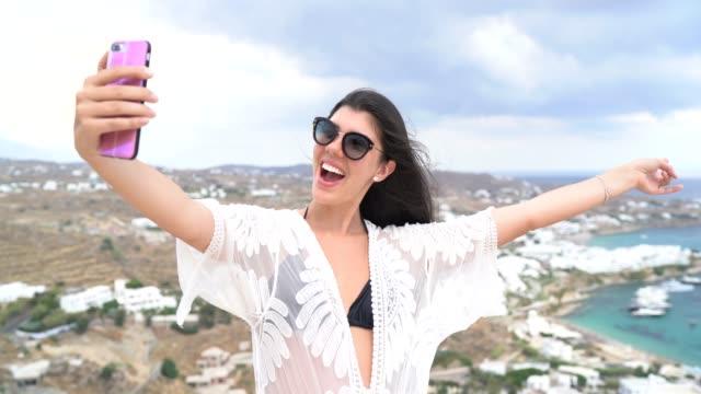 junge frau macht selfie mit smartphone in der spitze eines hügels, mykonos stadt und bucht auf dem hintergrund - achtlos stock-videos und b-roll-filmmaterial