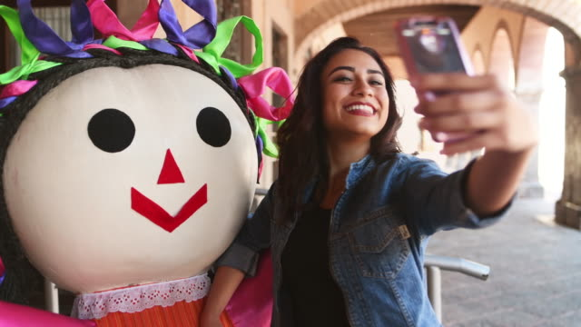 young woman taking selfie with traditional mexican doll - латинская америка стоковые видео и кадры b-roll