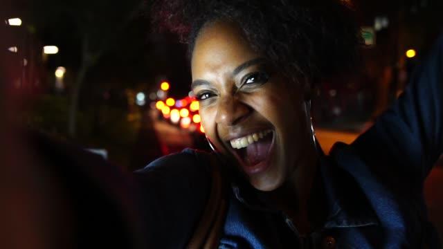 vídeos de stock, filmes e b-roll de jovem mulher tomar selfies na cidade à noite - brasileiro pardo