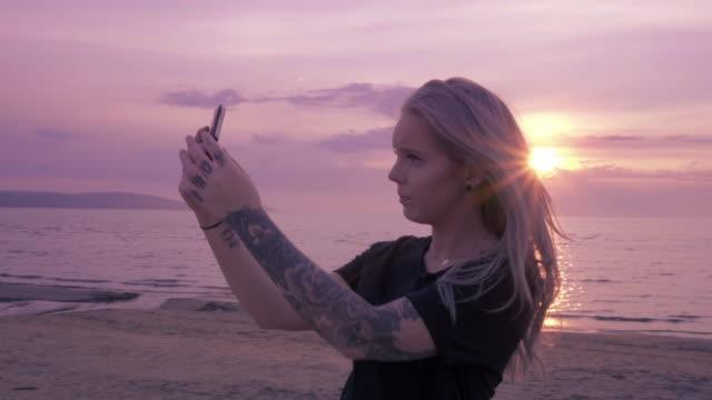 vídeos de stock, filmes e b-roll de jovem mulher tomando selfies na praia - temas fotográficos