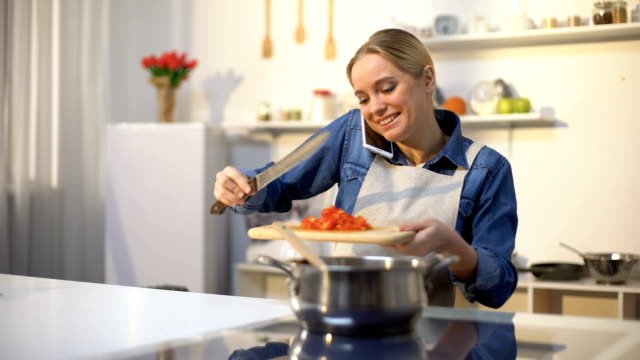 Young woman talking on phone and preparing tomato sauce, easy food recipe