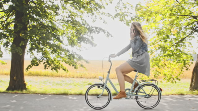 vídeos de stock e filmes b-roll de ts young woman talking on phone while cycling - saia