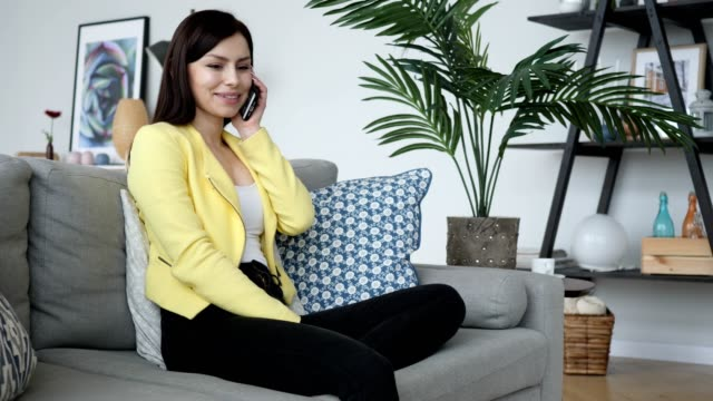 Young Woman Talking on Phone while Sitting on Couch video