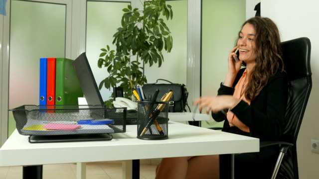 Young woman talking on the phone in the office video