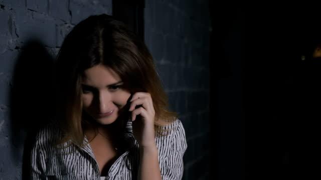 壁の近くの電話で話す若い女性 - 石垣点の映像素材/bロール