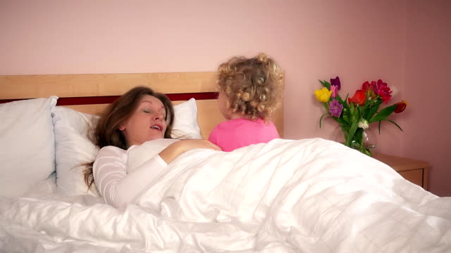 Young woman talking with her daughter girl in bedroom bed video