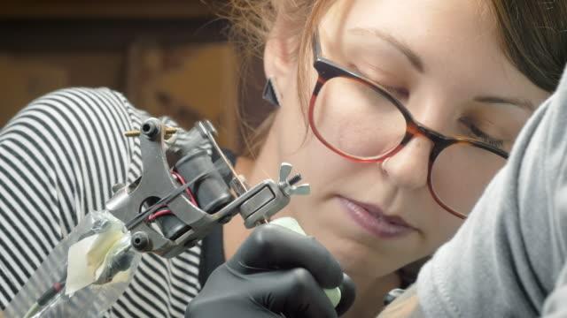 young woman tattoo artist giving someone a tattoo in 4k - tatuaż filmów i materiałów b-roll