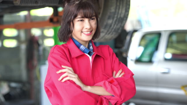 Young woman technician in garage pose arms crossed , pride and success gesturing