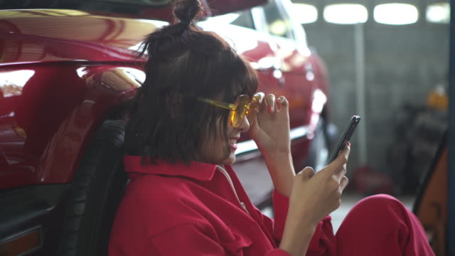 Young woman technician in garage using smartphone  , red uniform