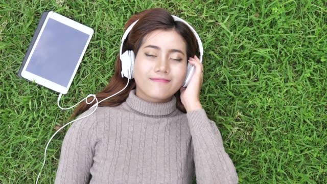 Young woman teenager enjoying favorite music at headphones lying on grass
