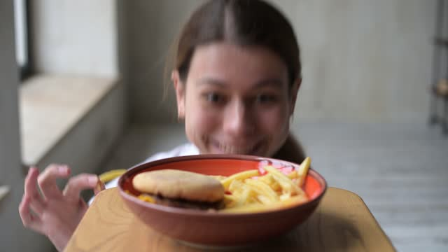 ung kvinna frestad av skräp snabbmat och tar pommes frites från tallrik - fett näringsämne bildbanksvideor och videomaterial från bakom kulisserna