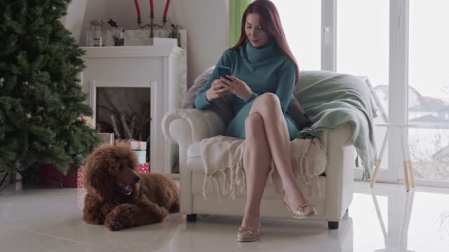 Young woman text messaging her friends while relaxing in her living room with her dog