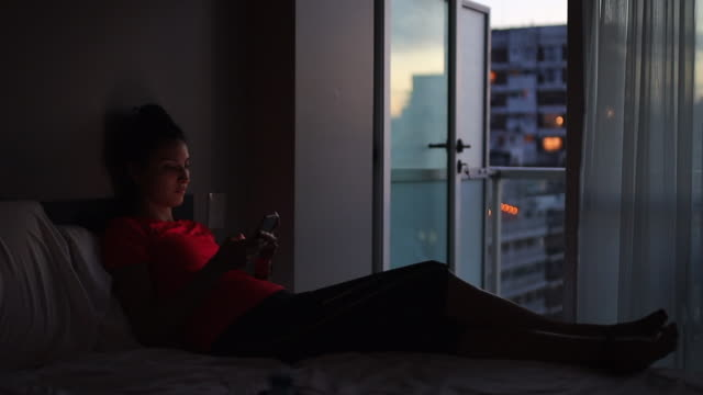 young woman texting in bed Young woman texting in her bed, relaxing, after a day at work. low lighting stock videos & royalty-free footage