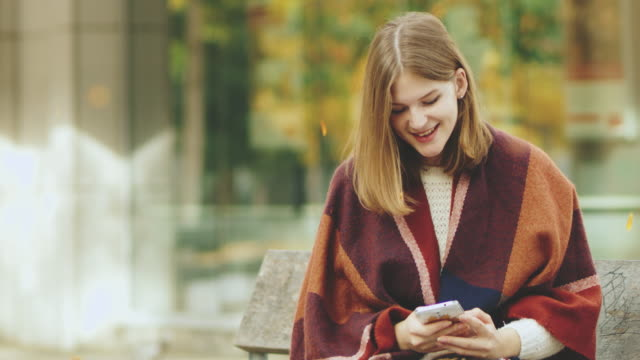 ms young woman texting with smart phone in autumn park - soft focus video stock e b–roll