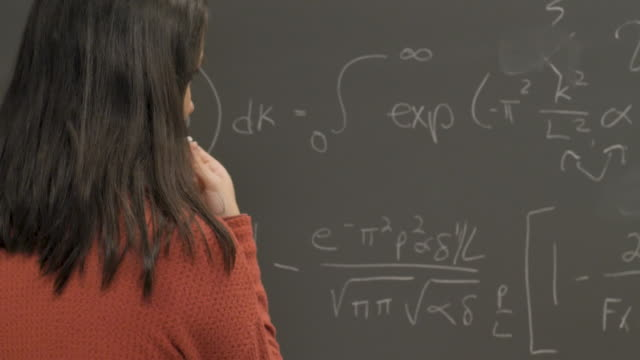 young woman thinking about a complicated problem on a chalkboard - formula 1 стоковые видео и кадры b-roll