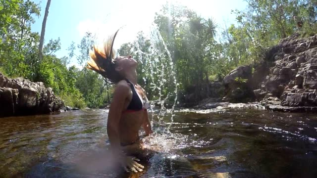 Young woman tossing wet hair in water video