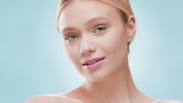 Young woman touches shoulder and clavicles looking at the camera Young fit good-looking European woman with light hair touches her shoulder and clavicles looking at the camera and smiling against blue ripple background | Skincare cosmetics advertisement lip balm stock videos & royalty-free footage