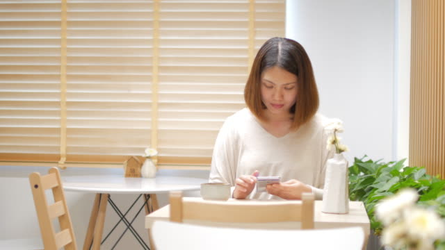Young woman touching and using smartphone at relaxing time in coffee cafe , dolly shot right to left video