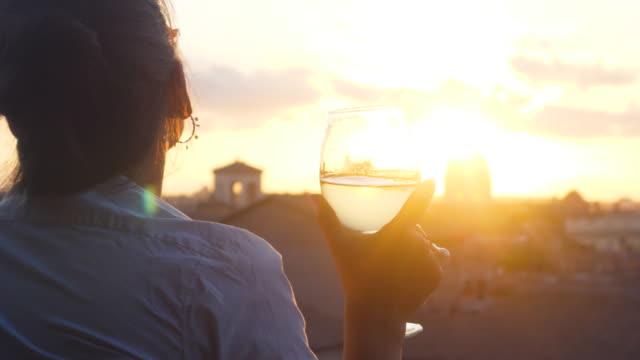 junge frau touristen mode weißes kleid mit glasigen weißwein vor dem panoramablick auf das stadtbild von rom stadtbild von campidoglio terrasse bei sonnenuntergang. sehenswürdigkeiten, kuppeln von rom, italien. - weinglas stock-videos und b-roll-filmmaterial