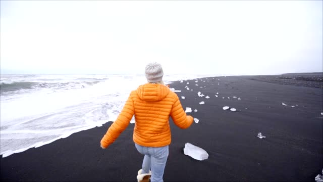 Young woman tourist female skipping and frolicking on black sand beach at Jokulsarlon Diamond's beachx video