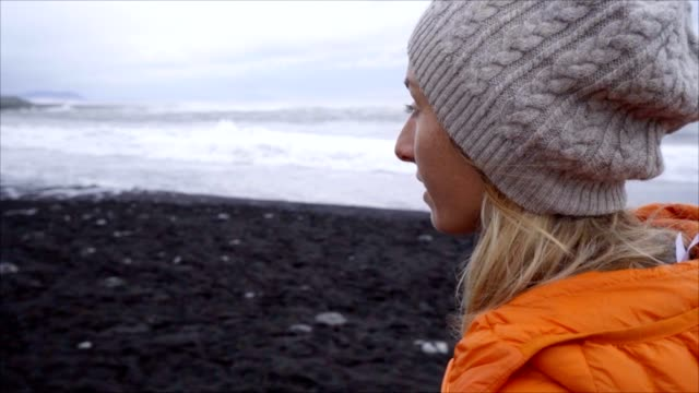Young woman tourist female walking on black sand beach at Jokulsarlon Diamond's beach video