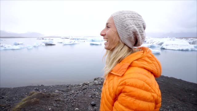 Young woman tourist female walking on by glacier lagoon at Jokulsarlon beach video