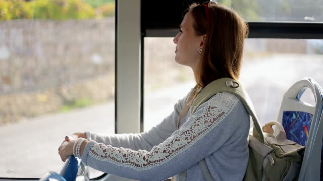 Young woman tourist go by bus with backpack sitting indoors, looking in window video