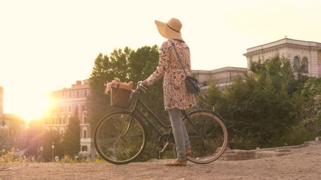 Young woman tourist with bycicle takes pictures of the colosseum in rome at sunset with smartphone. Beautiful stylish dress with large hat, flowers and bread in basket video