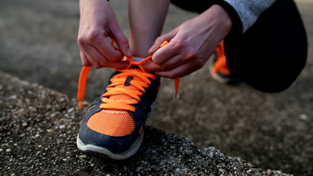 young woman trail runner tying shoelaces