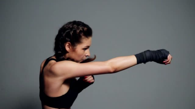 Young woman training with her hands wrapped in boxing tapes isolated on grey background. Slowmotion shot video