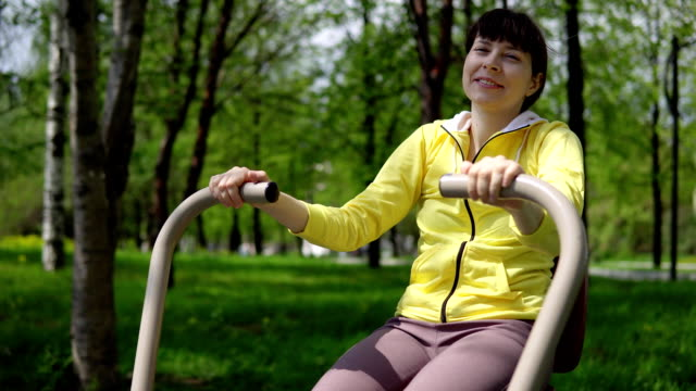 Young woman trains on stationary simulators in the open air. Young attractive woman trains on stationary outdoor simulators in the summer day. bodyweight training stock videos & royalty-free footage