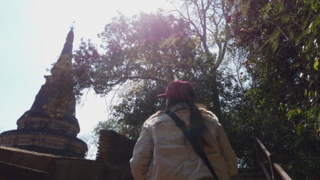Young Woman travel in old temple and Buddha head statue