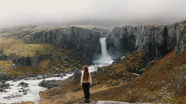 giovane viaggiatrice che esplora il pittoresco canyon di montagna con cascata in islanda - grandangolo composizione cinematografica video stock e b–roll