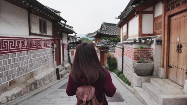 vídeos de stock e filmes b-roll de young woman traveler take a photo by smartphone and traveling into bukchon hanok village at seoul city, south korea - seul