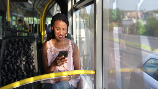 Young woman traveling by a bus and using smart phone video