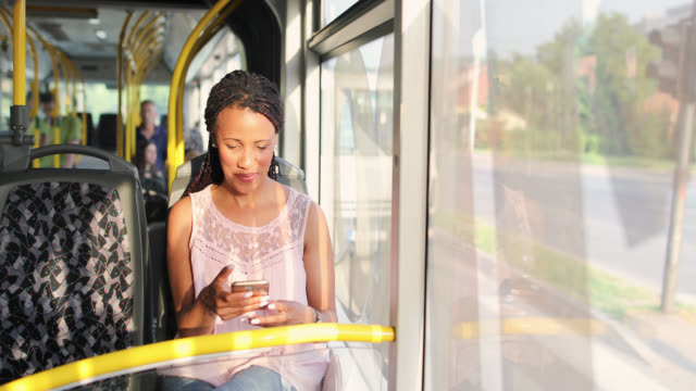 Young woman traveling by a bus and using smart phone Young woman traveling by a bus and using smart phone bus stock videos & royalty-free footage