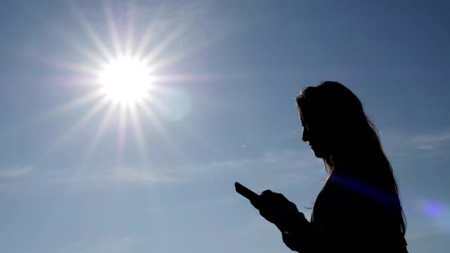 A young woman traveller calling on the mobile phone, bright sun, clear blue sky, silhouette, slow motion