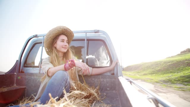young woman travelling in the back of a pick-up truck - cowgirl video stock e b–roll