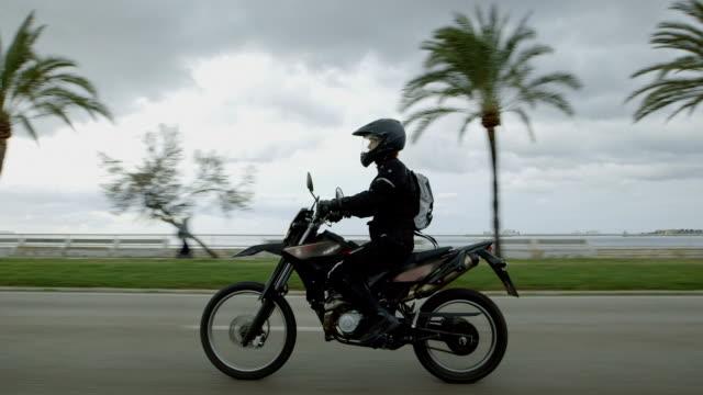 Junge Frau auf einem Motorrad unterwegs. Tropisches Klima – Video