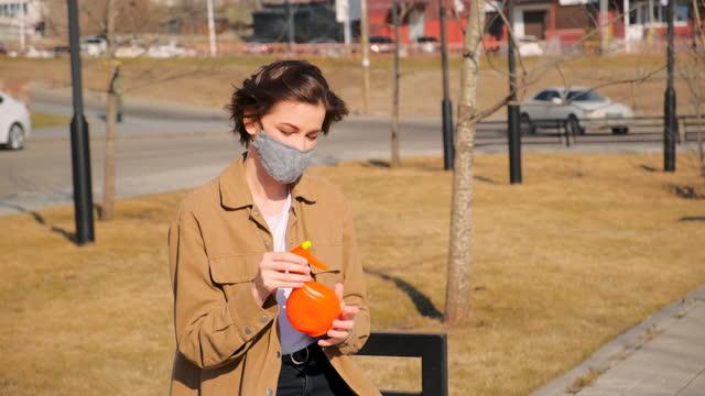 молодая женщина лечит руки дезинфицирующим средством - covid testing стоковые видео и кадры b-roll