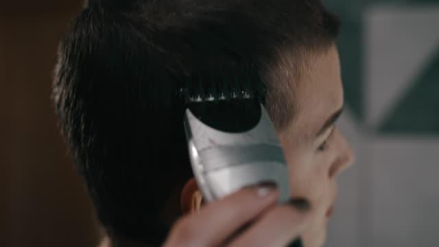 ms junge frau trimmt ihre haare zu hause während der quarantänezeit - friseur lockdown stock-videos und b-roll-filmmaterial