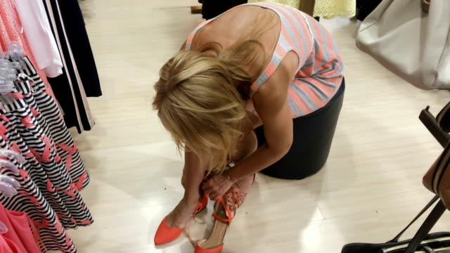 Young woman try on shoes in the shop video
