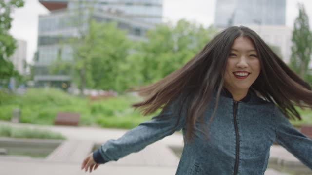 vídeos de stock, filmes e b-roll de jovem mulher virando e sorrindo ao lado de arranha-céu - somente japonês