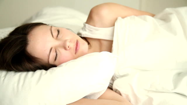 vídeos y material grabado en eventos de stock de mujer joven girando y lanzando en su sueño - almohada