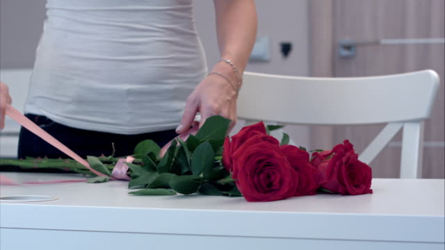 Young woman tying a ribbon bow on red rose bouquet video