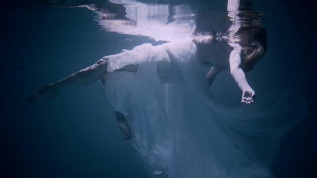 stockvideo's en b-roll-footage met jonge vrouw onder het water, ze draagt een witte jurk. - woman water