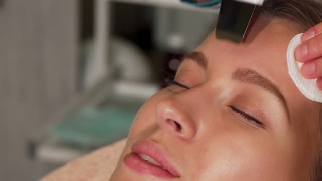 Young woman undergoing ultrasonic facial treatment at beauty salon Young woman undergoing ultrasonic facial treatment at beauty salon. Cropped shot of a female client having her cosmetology treatment done by professional beautician using ultrasonic tools. beautician stock videos & royalty-free footage